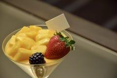 Ένα ποτήρι του επιδορπίου πολυτέλειας φρούτων και του θολωμένου υποβάθρου στοκ εικόνα