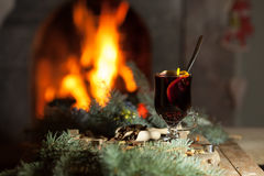 Ένα ποτήρι του θερμαμένων κρασιού και των καρυκευμάτων σε ένα υπόβαθρο μιας καίγοντας εστίας Στοκ εικόνες με δικαίωμα ελεύθερης χρήσης
