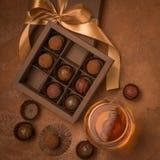 Ένα ποτήρι του κονιάκ και των σοκολατών σε μια κορδέλλα σατέν διακοσμήσεων κιβωτίων εγγράφου Επίπεδο σχεδιάγραμμα Τετραγωνικό πλα στοκ φωτογραφίες με δικαίωμα ελεύθερης χρήσης