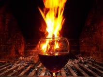 Ένα ποτήρι του κρασιού γύρω από μια πυρκαγιά στη χειμερινή εποχή στοκ φωτογραφία με δικαίωμα ελεύθερης χρήσης