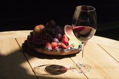 Ένα ποτήρι του κόκκινου κρασιού σε έναν ξύλινο πίνακα και ώριμα φρούτα στοκ φωτογραφίες
