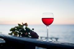 Ένα ποτήρι του κόκκινου κρασιού στο ηλιοβασίλεμα στο πεζούλι Στοκ Εικόνα