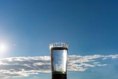 Ένα ποτήρι του νερού ενάντια σε έναν μπλε ουρανό Στοκ Φωτογραφία