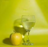 Ένα ποτήρι του νερού και η κίτρινη Apple σε ένα πράσινο υπόβαθρο Στοκ Φωτογραφία