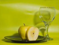 Ένα ποτήρι του νερού και της κίτρινης Apple στο πιάτο στο πράσινο υπόβαθρο Στοκ φωτογραφία με δικαίωμα ελεύθερης χρήσης