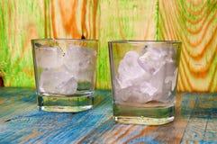 Ένα ποτήρι του ουίσκυ με τον πάγο στο αφηρημένο ξύλινο υπόβαθρο Στοκ Εικόνα