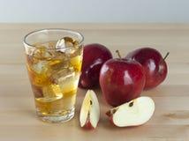 Ένα ποτήρι του φρέσκου κρύου χυμού της Apple με τον πάγο εκτός από τα μήλα σε ένα Wo Στοκ Εικόνες