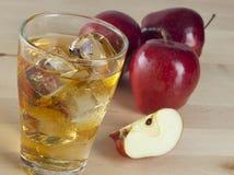 Ένα ποτήρι του φρέσκου κρύου χυμού της Apple με τον πάγο εκτός από τα μήλα σε ένα Wo Στοκ φωτογραφίες με δικαίωμα ελεύθερης χρήσης