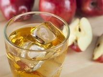 Ένα ποτήρι του φρέσκου κρύου χυμού της Apple με τον πάγο εκτός από τα μήλα σε ένα Wo Στοκ εικόνα με δικαίωμα ελεύθερης χρήσης
