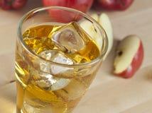 Ένα ποτήρι του φρέσκου κρύου χυμού της Apple με τον πάγο εκτός από τα μήλα σε ένα Wo Στοκ Φωτογραφίες