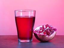 Ένα ποτήρι του χυμού ροδιών με τα φρούτα ροδιών στον ξύλινο πίνακα Υγιής έννοια ποτών Στοκ Φωτογραφίες