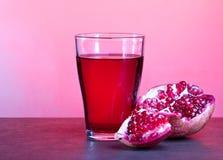 Ένα ποτήρι του χυμού ροδιών με τα φρούτα ροδιών στον ξύλινο πίνακα Υγιής έννοια ποτών Στοκ Φωτογραφία