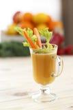 Ένα ποτήρι του χυμού στις κούπες ενός γυαλιού latte με κομμάτια του σέλινου και τα καρότα με ένα χρωματισμένο υπόβαθρο Στοκ Εικόνες