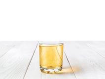 Ένα ποτήρι του χυμού της Apple στο άσπρο γραφείο Στοκ εικόνες με δικαίωμα ελεύθερης χρήσης