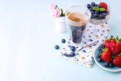 Ένα ποτήρι του chia καφέ και πουτίγκας με τα βακκίνια και φράουλες για τα χορτοφάγα τρόφιμα προγευμάτων η ανθοδέσμη εμβλημάτων αν Στοκ Εικόνες