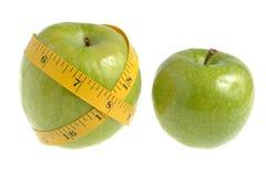Ένα πράσινο μήλο που τυλίγεται με τη μέτρηση της ταινίας και ενός άλλου πράσινου AP Στοκ Φωτογραφία