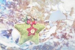 Ένα πράσινο πλεκτό αστέρι στο Σκανδιναβικό ύφος κρεμά σε έναν κλάδο με το χιόνι απομονωμένο λευκό παιχνιδιών σφαιρών Χριστουγέννω Στοκ Εικόνες
