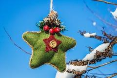 Ένα πράσινο πλεκτό αστέρι στο Σκανδιναβικό ύφος κρεμά σε έναν κλάδο με το χιόνι απομονωμένο λευκό παιχνιδιών σφαιρών Χριστουγέννω Στοκ φωτογραφία με δικαίωμα ελεύθερης χρήσης