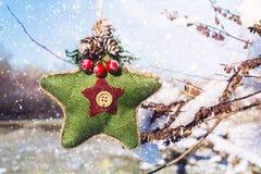 Ένα πράσινο πλεκτό αστέρι στο Σκανδιναβικό ύφος κρεμά σε έναν κλάδο με το χιόνι απομονωμένο λευκό παιχνιδιών σφαιρών Χριστουγέννω Στοκ φωτογραφίες με δικαίωμα ελεύθερης χρήσης
