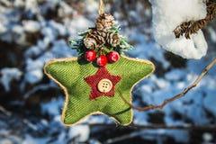 Ένα πράσινο πλεκτό αστέρι στο Σκανδιναβικό ύφος κρεμά σε έναν κλάδο με το χιόνι απομονωμένο λευκό παιχνιδιών σφαιρών Χριστουγέννω Στοκ Φωτογραφία