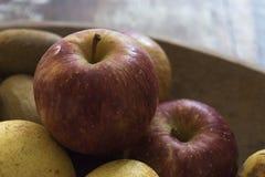Ένα πραγματικό οργανικό κόκκινο μήλο με άλλα φρούτα σε έναν ξύλινο δίσκο στοκ εικόνες με δικαίωμα ελεύθερης χρήσης