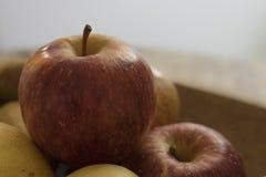 Ένα πραγματικό οργανικό κόκκινο μήλο με άλλα φρούτα σε έναν ξύλινο δίσκο στοκ εικόνα