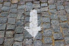 Ένα προς τα κάτω βέλος που χρωματίστηκε με το άσπρο χρώμα στο παλαιό πεζοδρόμιο stoneblock με τους τετραγωνικούς φραγμούς γρανίτη Στοκ εικόνα με δικαίωμα ελεύθερης χρήσης