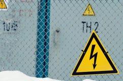 Ένα προστατευτικό δίκτυο και σημάδια που προειδοποιούν για τον κίνδυνο ηλεκτρικού Στοκ Φωτογραφίες