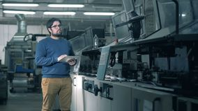 Ένα πρόσωπο ελέγχει το λειτουργώντας μεταφορέα σε ένα γραφείο εκτύπωσης απόθεμα βίντεο