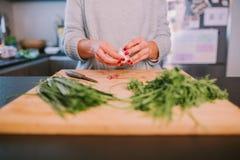 Ένα πρόσωπο μαγειρεύει τα λαχανικά στοκ εικόνα