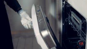Ένα πρόσωπο με ένα κυβερνητικό χέρι ανοίγει ένα πλυντήριο πιάτων απόθεμα βίντεο
