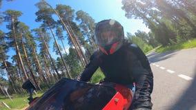 Ένα πρόσωπο οδηγεί μια μοτοσικλέτα κατά μια μπροστινή άποψη απόθεμα βίντεο
