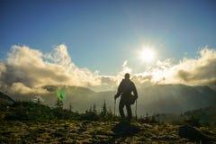 Ένα πρόσωπο που στέκεται στο βουνό με τα σύννεφα κατά τη διάρκεια του ηλιοβασιλέματος/Sunr Στοκ φωτογραφία με δικαίωμα ελεύθερης χρήσης