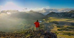 Ένα πρόσωπο που στέκεται στο βουνό με τα σύννεφα κατά τη διάρκεια του ηλιοβασιλέματος/Sunr Στοκ Φωτογραφία