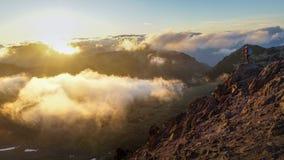 Ένα πρόσωπο που στέκεται στο βουνό με τα σύννεφα κατά τη διάρκεια του ηλιοβασιλέματος/Sunr Στοκ εικόνα με δικαίωμα ελεύθερης χρήσης