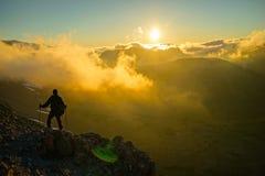 Ένα πρόσωπο που στέκεται στο βουνό με τα σύννεφα κατά τη διάρκεια του ηλιοβασιλέματος/Sunr Στοκ Εικόνες