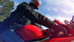 Ένα πρόσωπο σε ένα κράνος οδηγά μια κόκκινη μοτοσικλέτα απόθεμα βίντεο