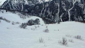 Ένα πρόσωπο στο σνόουμπορντ κάτω από το λόφο, που ζαλίζει το βουνό στο υπόβαθρο φιλμ μικρού μήκους