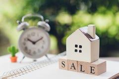Ένα πρότυπο πρότυπο σπιτιών τοποθετείται στην ξύλινη πώληση λέξης σαν έννοια ακίνητων περιουσιών ιδιοκτησίας υποβάθρου με το διάσ στοκ εικόνες