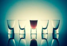 Ένα πλήρες πυροβοληθε'ν γυαλί με το ποτό οινοπνεύματος με την αντανάκλαση δίπλα στο τ Στοκ Εικόνες