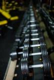 Ένα πλήρες σύνολο αλτήρων, εξοπλισμού που χρησιμοποιούνται στην κατάρτιση βάρους και ρουτινών καθορίζω-βάρους σε ένα σκοτεινό θολ Στοκ εικόνες με δικαίωμα ελεύθερης χρήσης