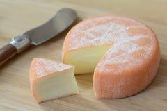 Ένα πλήρες brie ροδών τυρί με μια φέτα περικοπών και ένα μαχαίρι Στοκ φωτογραφία με δικαίωμα ελεύθερης χρήσης