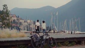 Ένα ρομαντικό ζεύγος περπατά κάτω από την ακτή το καταπληκτικά βράδυ, τα γιοτ, την πόλη και τα βουνά στο backgroun απόθεμα βίντεο