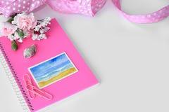 Ένα ρόδινο σημειωματάριο με μια μικροσκοπική ζωγραφική watercolor παραλιών Στοκ Φωτογραφία