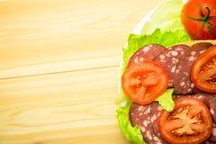 Ένα σάντουιτς με το λουκάνικο και μια ντομάτα στα φύλλα μαρουλιού Στοκ Φωτογραφίες