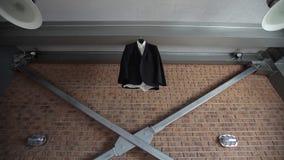 Ένα σακάκι και ένα κοστούμι ατόμων ` s κρεμούν σε μια κρεμάστρα κοντά σε έναν τούβλινο τοίχο πριν από το γάμο νεόνυμφων ` s απόθεμα βίντεο