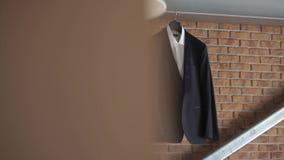 Ένα σακάκι και ένα κοστούμι ατόμων ` s κρεμούν σε μια κρεμάστρα πριν από το γάμο νεόνυμφων ` s απόθεμα βίντεο