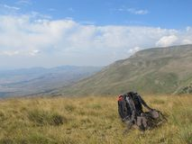 Ένα σακίδιο πλάτης στο έδαφος με πίσω από τα βουνά της Αλβανίας στοκ φωτογραφία