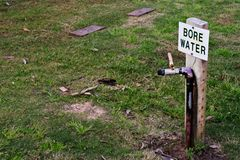Ένα σημάδι για άντεξε το νερό στη μέση ενός στεγνωμένου χορτοτάπητα Στοκ φωτογραφία με δικαίωμα ελεύθερης χρήσης