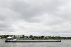 Ένα σκάφος στο δρόμο του πέρα από τον ποταμό του Ρήνου κατά μήκος των σπιτιών και του φυσικού Ρήνου riverbank στοκ εικόνες